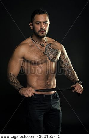 Going To Punish You. Fashion Model With Leather Belt. Man With Tattoo. Bearded Man With Muscular Tor