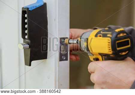 Builder Is Installing Lock A Doot In The Room Installation Into Wood Door