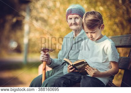 Young Boy Reading Book On Bench In Park. His Great Grandmother Sitting Next To Him.