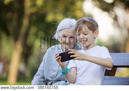 Young Boy And His Great Grandmother Using Smartphone To Take Selfie. Making Video Call. Streaming On