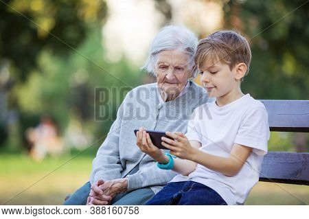 Young Boy And His Great Grandmother Watching Video On Smartphone. Using Smartphone To Take Selfie. M