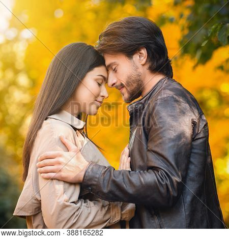 Portrait Of Young Couple In Love Cuddling Over Autumn Forest Background, Embracing And Touching Each