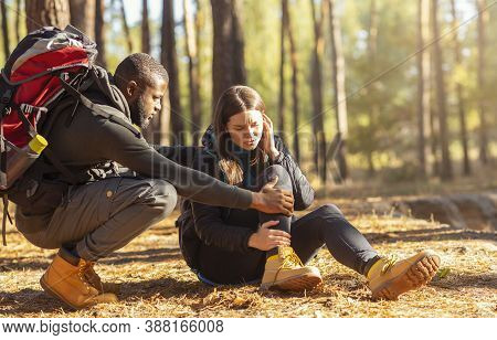 African Man Comforting His Upset Caucasian Girlfriend, Woman Hurt Her Ancle While Camping In Forest,