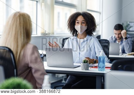 Finding Customers And Employees After Lockdown. African American Woman In Protective Mask At Desk Wi