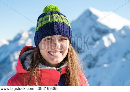 Portrait Of A Woman In A Winter Hat With A Pom-pom On A Background Of Mountain
