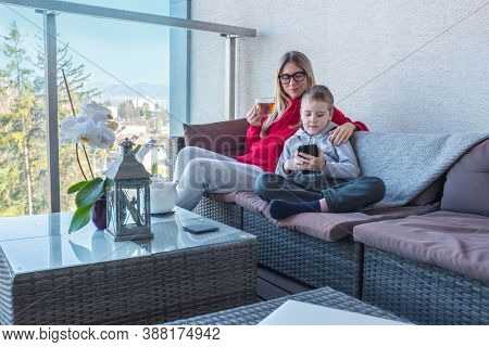 Stay at home mom. Mother and son spend free time on terrace. Woman working, child using smartphone. Weekend Family. Bonding concept.