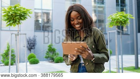 African American Joyful Young Stylish Woman Tapping Or Scrolling On Tablet Device And Standing At Ci