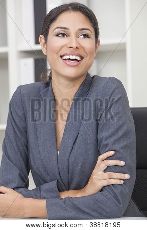 Beautiful happy young Latina Hispanic woman or businesswoman in smart business suit sitting at a desk in an office laughing