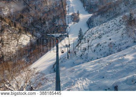 Hokkaido, Japan - December 2019 : Area Of Kiroro Ski Resort. Skiers And Snowboarders Ride The Gondol