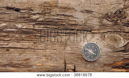 Compass on the old wooden background
