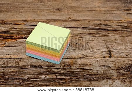 Vibrant block of colorful post it notes on wooden background
