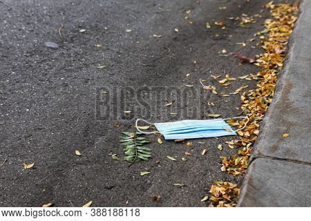 Blue used protective mask on street in COVID-19 pandemic