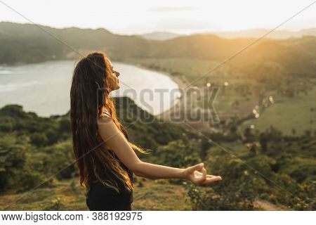 Young Woman Practicing Yoga Poses At Sunset With Beautiful Ocean And Mountain View. Sensitivity To N