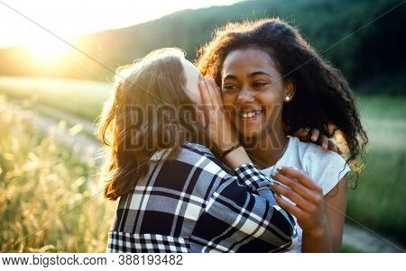 Young Teenager Girls Friends Outdoors In Nature, Whispering In Ear.