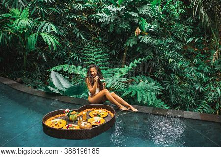 Girl Relaxing And Eating Floating Breakfast In Jungle Pool On Luxury Villa In Bali. Valentines Day O