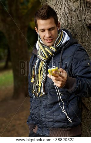 College student in park using mp3 player at autumn.