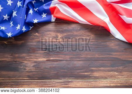 Close-up Of The American Flag Is Placed On The Left Side With Copy Space On A Wooden Table Backgroun