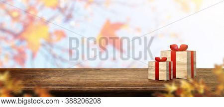 Autumn Background.gift Box On Old Rustic Wood Table With Blur Forest Tree With Sunlight,autumn Fall