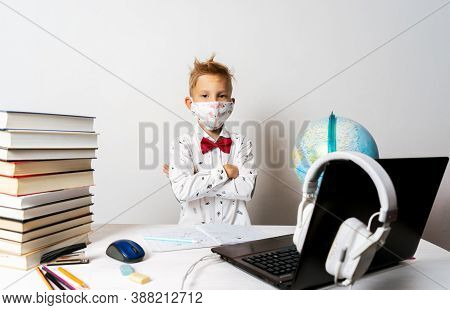 A Boy In Quarantine Wearing A Mask With A Laptop Is Undergoing School Training Remotely.