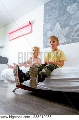 A Small Boy In Rough-soled Sneakers Is Sitting On A White Sofa.