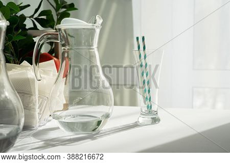 A Clear Glass Carafe Of Water And A Glass With Striped Tubes On A Table With A White Tablecloth In T