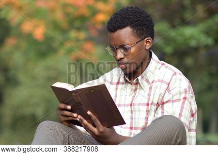 Portrait Of Serious Concentrated Young Black African Afro American Intelligent Man, Student In Glass