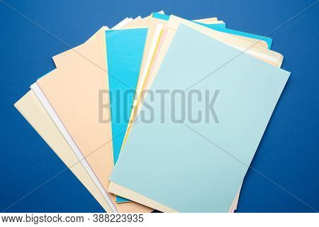 Stack Of Multi-colored Paper Colored Sheets On A Blue Background, Top View