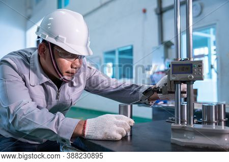 Asian Technician Worker Wearing A Safety Suit And Quality Checking With Hight Gauge Mass Product On