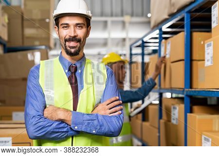 Portrait of Middle east Turkish White caucasian warehouse manager crossed arm with his worker working in background in warehouse distribution center environment. Business warehouse inventory concept.