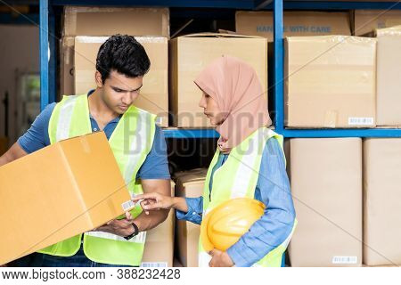 Islam asian warehouse worker working with Indian warehouse worker about inventory and checking on barcode. For business warehouse inventory logistic and diversity interracial teamwork concept.
