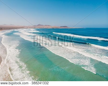 Aerial View Of Famara Beach With Blue Ocean And Surfing Waves In Lanzarote, Canary Islands