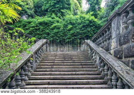 Old Stone Staircase In The Park. Ancient Staircase Are Grey Stone With Stone Balusters On A Backgrou