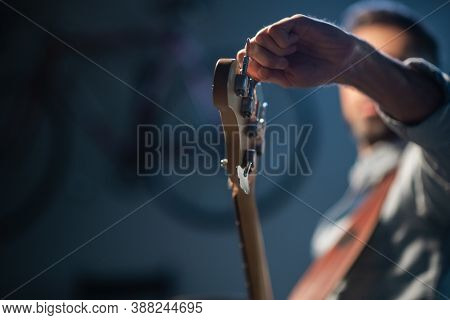 The Bassist Adjusts The Electric Bass Guitar, In The Foreground Of The Pegs And Fretboard, Close-up