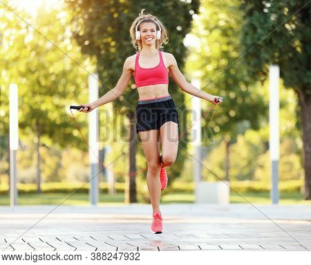 Full Length Of Positive Energetic Slim Female In Sportive Outfit And Headphones Jumping With Skippin