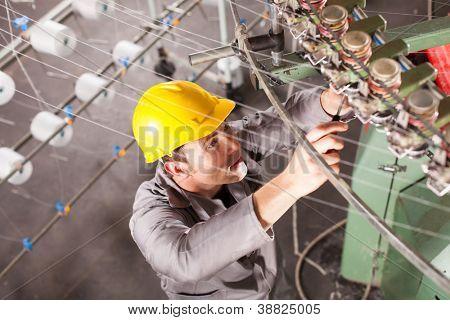 textile company technician repairing weaving machine