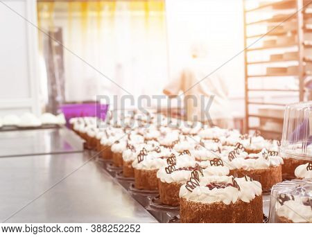 Making Sponge Cakes With Cream At A Confectionery Factory. Cook Decorates Cake With Cream, Sweet Des