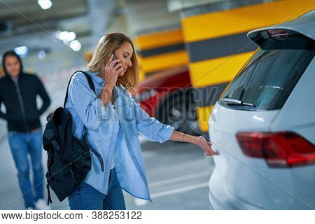 Criminal man in black hoodie approaching young woman opening car on parking