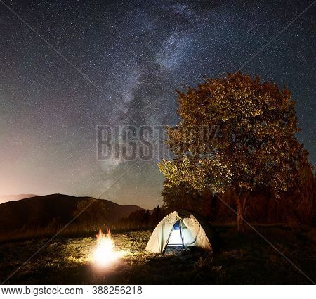 Tourist Camping Near Forest At Summer Night. Glowing Tent And Bonfire Under Amazing Night Sky Full O