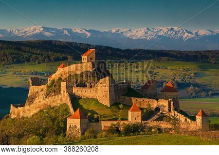Famous Rupea Fortress At Sunrise. Stunning Castle And High Snowy Fagaras Mountains In Background, Br