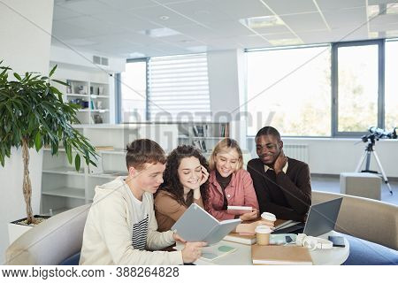 Multi-ethnic Group Of Cheerful Young People Studying Together While Sitting At Table In College Libr