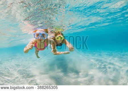 Young Mother With Child In Snorkeling Mask Dive In Coral Reef Sea Lagoon To Explore Underwater World