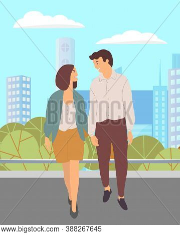 Young Couple, Short-haired Girl And Guy In Brown Trousers Walk In City Park. Lovers Meet Outdoor. Gr