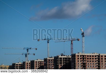 Cranes On Building Construction On Blue Sky Background