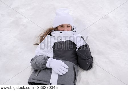 Beautiful Small Girl In Warm Clothing Lean On White Snow During Winter Vacation On Ski Resort With C