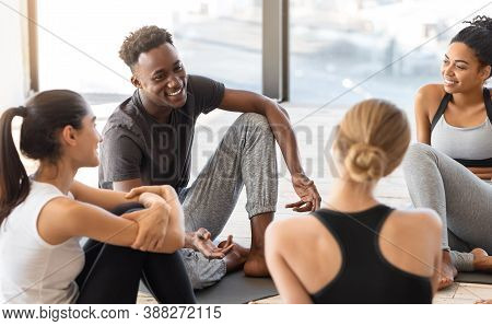 Multiethnic Group Of People Sitting On Mats Relaxing After Yoga Training In Modern Studio, Chatting
