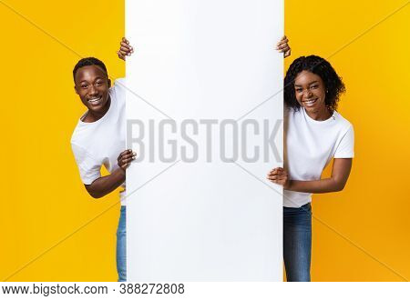 Cheerful African American Couple In Love Holding Empty Board For Advertisement Or Text Over Yellow S