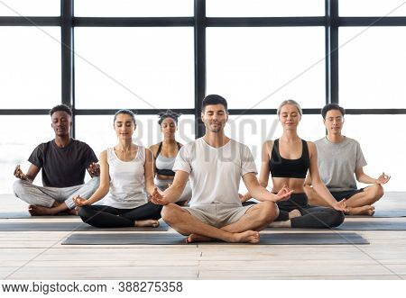 Group Meditation. Young Multiethnic Men And Woman Meditating Together In Lotus Position In Modern St