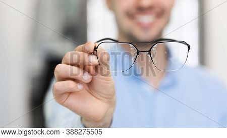 Eyesight And Vision Concept. Closeup Of Unrecognizable Happy Man Customer Showing New Eyeglasses At