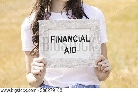 Financial Aid Text Written On A Card In Hands.