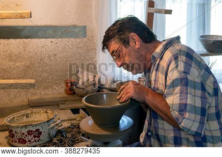 Horezu, Romania - July 23, 2020: Traditional Artist In Folk Art Shaping A Clay Pot With Hands.